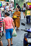 06 JUNE 2013 - BANGKOK, THAILAND:    A Buddhist monk walks along Krung Kasem Rd during his morning alms rounds in front of Bobae Market in Bangkok.  Bobae Market is a 30 year old market famous for fashion wholesale and is now very popular with exporters from around the world. Bobae Tower is next to the market and  advertises itself as having 1,300 stalls under one roof and claims to be the largest garment wholesale center in Thailand.       PHOTO BY JACK KURTZ