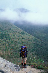 Backpacking.  A hiker looks across the foggy valley at the Franconia Ridge.  Old Bridle Path Trail, White Mtns, NH