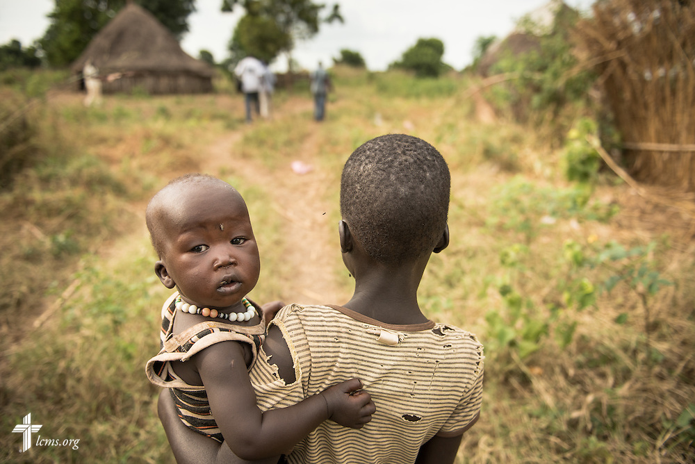 A child carries a baby on Wednesday, Sept. 23, 2015, at the Leitchour Refugee Camp outside Gambela, Ethiopia. LCMS Communications/Erik M. Lunsford