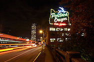 Lights illuminate the Pearl Disctrict and a large neon sign reads Portland, Oregon.