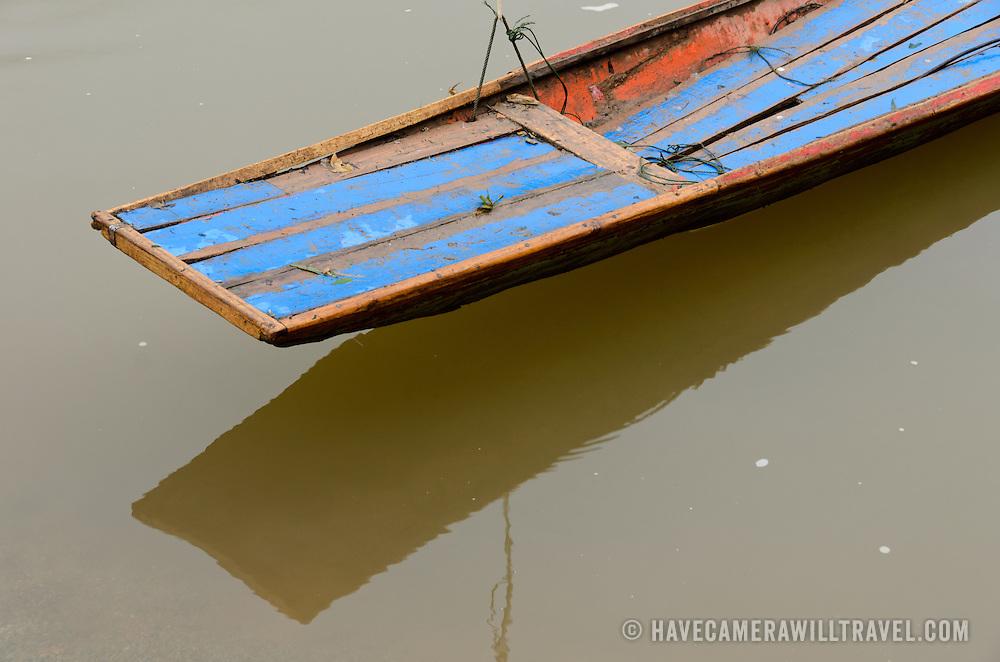 Detail of the end of a long, thin, wooden boat on the brown waters of the Nam Ou (River Ou) in northern Laos.