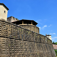 Fortezza Da Basso Wall in Florence, Italy<br /> The Fortezza Da Basso, which was finished in 1537, has massive walls that give the huge fortress a pentagonal shape.  It also features an imposing tower as seen from the Porta Santa Maria Novella entrance.  It never saw battle.  I was surprised to learn that this military Renaissance architecture is now an exhibition center that houses two modern pavilions with a contemporary appearance.  Two other Congress Centers managed by Firenze Fiera are nearby.