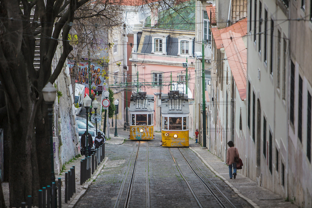 The Glória lift tram crossing in Lisbon. Glória lift tram is one of the three working climbing lifts in Lisbon.
