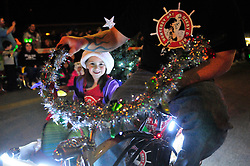 A bicycle with a sidecar was elegant transportaion for this young girl and her Christmas tree during Sunday night's 2013 Holiday Parade of Lights along Main Street in Salinas.