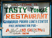 Tasty Tongue Restaurant sign in the Annapurna Conservation Area of Nepal.