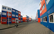 "Living In Containers<br /> By Ton Koene<br /> <br /> The Netherlands is a country with one the highest population density. Especially in the 'randstad', the heart of the Dutch ecomony, consist of Amsterdam, Rotterdam, Utrecht and Den Haag (7 million people) . The Randstad is together with London, Paris, the Flemish Diamond and the German Rhine / Ruhr area one of the main urban concentrations in northwest Europe. <br /> <br /> The area has turned into a busy beehive were land is scars and every square meter needs to be used effectively. Prices of land and housing have gone through the roof. As a result, many families have decided to leave this congested area and move to villages and towns less populated. <br /> <br /> However, many do need to live in this economical heart as they have jobs there or study. Talking about students: serious shortage of cheap housing has made it problematic for students to find accommodation. A company in Holland (Tempo housing) has found a solution: Keetwonen (keet=container, wonen=living). <br /> <br /> In 2007, they built a small city out of containers just outside the centre of Amsterdam; Over 1000 used sea containers have been converted into apartments and stacked as Lego blocks onto each other. It is the biggest container village ever built in the world. Tempo housing has designed, developed and built these temporary housing units especially for students. <br /> <br /> Living in a converted shipping container is a new concept in the Netherlands. It turned out to be a big success under students in Amsterdam and it is now one of the most popular student dormitories in the Netherlands. The student housing foundation ""De Key"" (www.dekey.nl) in Amsterdam takes care of the administration and supervises the buildings. There is an official waiting time of 2 years but most students can move in much faster. In fact most students who inhabited the containers have been living here from the beginning when the units were built.<br /> <br /> The early day's fears that the container homes are too small, too noisy, too co"