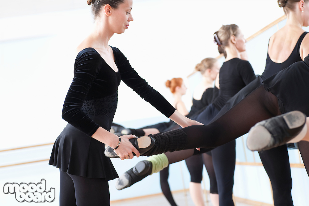 Ballet teacher adjusting foot position at the barre