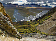 The Alaska Range rises above tundra and a braided river seen from near Polychrome Overlook, in Denali National Park, Alaska, USA.