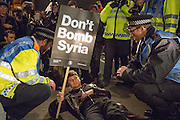 UNITED KINGDOM, London: 02 December 2015 Thousands of people gather in Parliament Square this evening as part of a Stop The War campaign. Protesters have gathered outside Parliament for a second night as they await the result of a vote on UK air strikes in Syria. <br /> Pictured: A protester refuses to move after staging a 'die-in' outside of Parliament..<br /> Rick Findler / Story Picture Agency