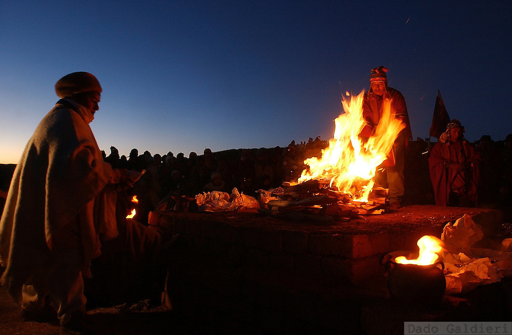 Aymara priests, or Yatiris, lights a ceremonial fire in which they burn alcohol, llama featuses, sugar and other sacred stuff before they welcome the first rays of morning sunlight celebrating their New Year in the archaeological and turistic city of Tiwanaku, nearly 70 km northeast of Bolivian capital La Paz on Saturday, June 21, 2003. Aymaras celebrate their 5511ft year and  consider June 21 the day that marks the winter solstice and Aymara New Year.
