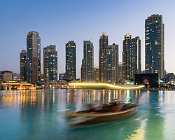 Night view of  luxury apartment towers and tourist boat trip on lake in Downtown Dubai United Arab Emirates