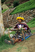 Indigenous woman in colourful clothes, weaving on a loom Cusco, Peru