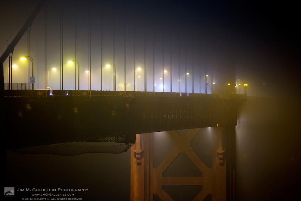 The Golden Gate Bridge immersed in fog at night aglow from street lights and traffic