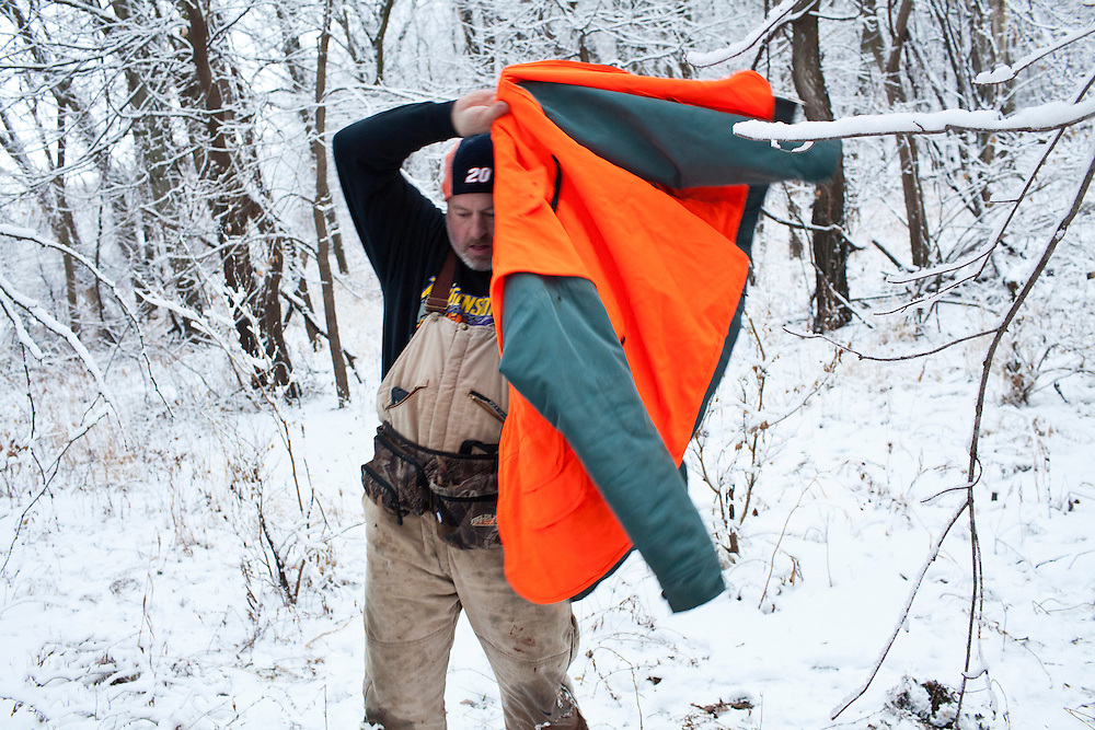Donovan Nokes puts on his coat after killing and field dressing a deer on Sunday, December 4, 2011 in Webster City, IA.