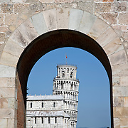 Leaning Tower viewed through Porta Nuova gate in city wall, Pisa, Tuscany, Italy