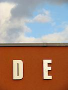 De, D E , ecrito, lettres sur un mur avec nuages. Buchstaben auf einer Mauer mit Wolkenhimmel. © Romano P. Riedo