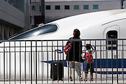 A mother and son watch a JR 700 class Shinkansen bullet train at leave Shin-Yokohama station, Yokohama, Japan. August 14th 2008