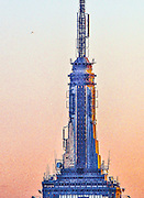 The rocketship-like, Art Deco spire of New York City's iconic Empire State Building at sunset, bristling with fins and antennae, while a jetliner can be seen in the background