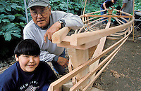 Inupiaq boy with father and whaling boat frame, Alaska Native Heritage Center Traditional Native Boat Project, Iñupiaq