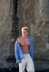 good looking blond man with an open shirt by cliffs