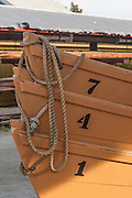 Numbered orange rowboats with bowlines attached stacked like chairs by the storage sheds