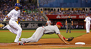 Los Angeles Angels first baseman Albert Pujols, right, dives to tag the bag as Kansas City Royals'  Alex Rios, left, runs to first base after a ground ball to the first baseman in the fourth inning of a baseball game at Kauffman Stadium in Kansas City, Mo., Friday, Aug. 14, 2015. (AP Photo/Colin E. Braley)