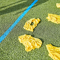A photograph of bibs and the shadow of a football player on the training pitches at St Georges park, the home of the England Football Team on a suny day