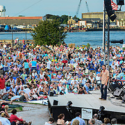 Prescott Park Arts Festival Executive Director Ben Anderson introduces a concert by Mary Chapin Carpenter and Marc Cohn in July, 2013, with the Piscataqua river in the background.