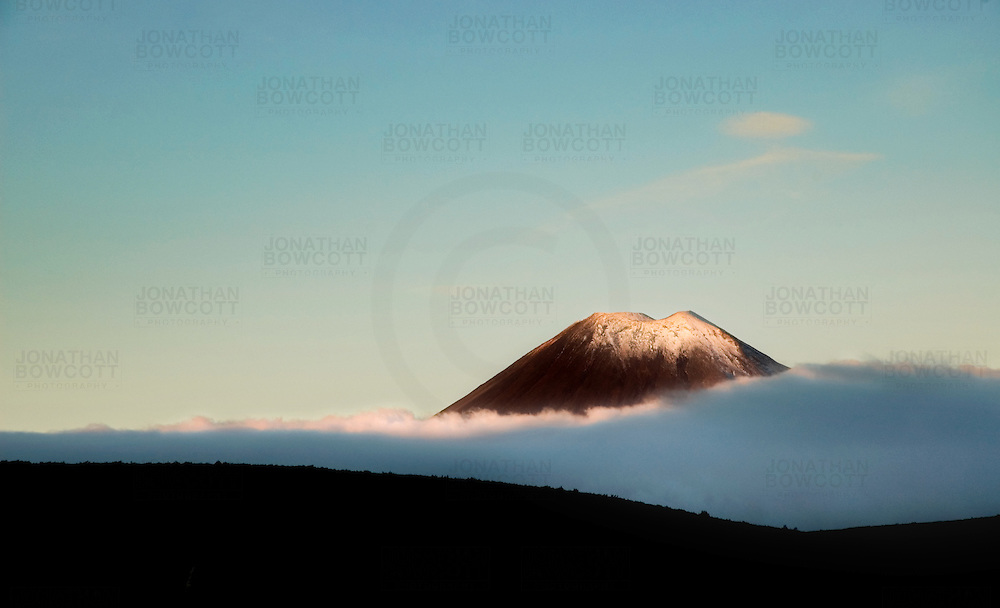 Mount Ngauruhoe is found on the North Island of New Zealand. It is the youngest vent in the Tongariro volcanic complex. It was used as the location for Mount Doom in The Lord of the Rings film trilogy. It lies between Mount Ruapehu to the south and Mount Tongariro to the north. This photograph, taken at sunset, was captured by Bristol based photographer Jonathan Bowcott