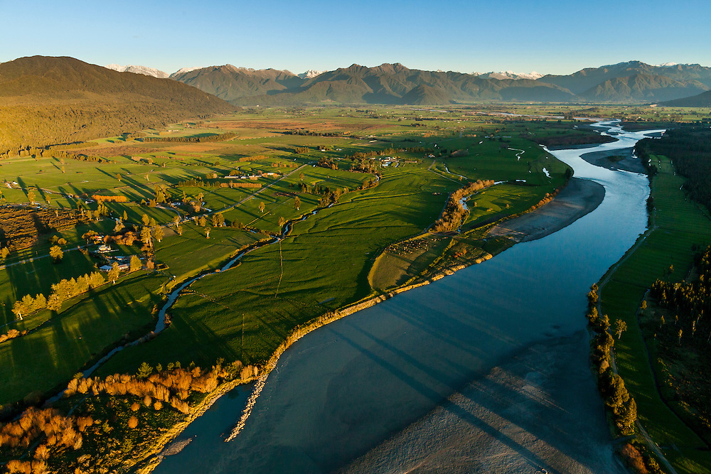 The Hokitika River and lush farmland with a backdrop of native bush clad mountains.