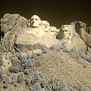 The Mount Rushmore National Memorial, near Keystone, South Dakota, is a monumental granite sculpture by Gutzon Borglum. The monument represents the first 150 years of the history of the United States of America with 60-foot (18 m) sculptures of the heads of former United States presidents (left to right): George Washington, Thomas Jefferson , Theodore Roosevelt, and Abraham Lincoln. The entire memorial covers 1,278.45 acres (5.17 km2) and is 5,725 feet (1,745 m) above sea level...This is an infrared image which captures light that we cannot see and turns it into a visible image. Plants like flowers and grass reflect more infrared light and appear brighter in infrared images while the sky reflects less making it darker.