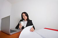 Businesswoman with coffee mug reading documents at desk in office