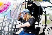 Woman driving mobile fish tricycle represents creatures living in water. MayDay Parade and Festival. Minneapolis Minnesota USA