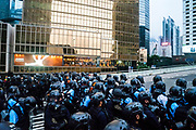 Riot police march forward as people look on from a Fairwood restaurant near the Central Government Offices, during a protest against a proposed extradition law in Hong Kong, SAR China, on Wednesday, June 12, 2019. Hong Kong's legislative chief postponed the debate on legislation that would allow extraditions to China after thousands of protesters converged outside the chamber demanding the government to withdraw the bill. Photo by Suzanne Lee/PANOS