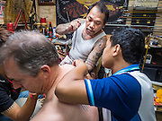 "27 MAY 2015 - BANGKOK, THAILAND: AJARN NENG ONNUT, gives a sacred Sak Yant tattoo to JOHN, a visitor to Thailand from the United States. Ajarn Neng is a revered master of sacred tattoos and sees people all day at his Bangkok home. Sak Yant (Thai for ""tattoos of mystical drawings"" sak=tattoo, yantra=mystical drawing) tattoos are popular throughout Thailand, Cambodia, Laos and Myanmar. The tattoos are believed to impart magical powers to the people who have them. People get the tattoos to address specific needs. For example, a business person would get a tattoo to make his business successful, and a soldier would get a tattoo to help him in battle. The tattoos are blessed by monks or people who have magical powers. Ajarn Neng, a revered tattoo master in Bangkok, uses stainless steel needles to tattoo, other tattoo masters use bamboo needles. The tattoos are growing in popularity with tourists, but Thai religious leaders try to discourage tattoo masters from giving tourists tattoos for ornamental reasons.     PHOTO BY JACK KURTZ"