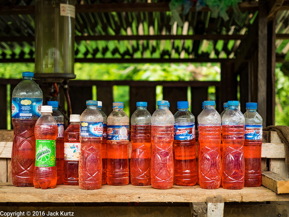 20 JUNE 2016 - DON KHONE, CHAMPASAK, LAOS:  Gasoline for sale in reused water bottles on Don Khone Island. Don Khone Island, one of the larger islands in the 4,000 Islands chain on the Mekong River in southern Laos. The island has become a backpacker hot spot, there are lots of guest houses and small restaurants on the north end of the island.    PHOTO BY JACK KURTZ