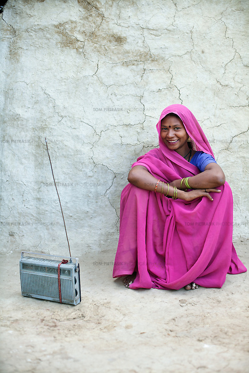 Pista, an Adivasi (tribal, or Scheduled Tribe) village of Patara, 20km from Shivpuri, listens to a radio outside her home. Pista is seven months pregnant with her fourth child. A survey recently found that half of all adult Adivasi residents in Shivpuri listen to the radio several times over the course of a day. The Adivasis are traditionally ostracised and many of them are illiterate so rely on the radio for news, information and entertainment. ..Shivpuri district in Madhya Pradesh suffers from poor health outcomes. Of particular concern is the high rate of maternal mortality. One of the Indian government's aims, with partners Unicef, is to encourage the population to adopt practices to improve sanitation and health practices. In an area made up of traditionally disadvantage groups and suffering low literacy rates, this can be a challenge. ..A survey found that radio was the most readily accessible media by the Shivpuri community with more than half saying they tuned in several times a day. ..Dharkan 107.8 FM will go on air in July. The station that will broadcast to 75 villages in a 15-kilometer radius reaching 170,000 people...Rather than preaching educational messages, the station, which is already producing pilot programs, uses humor and folk artists performing in the local language to entertain and inform their audiences. There is a major impact, especially on women, who are contributing their voices to such wide-ranging issues as caste discrimination, female feticide and women,A?o?s empowerment. ..Photo: Tom Pietrasik.Shivpuri, Madhya Pradeh. India.June 2009