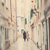 an older couple walk arm in arm along a venician street