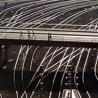 Rail yard. Backlit with light reflecting off rails. Six figures cross on a bridge.