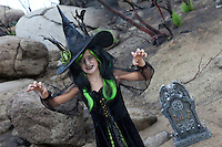 Girl in witch attire trying to scare you while standing in cemetery