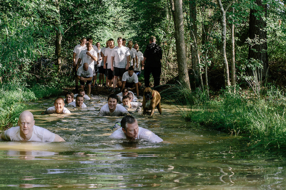 After swimming across a lake near Shipley's home, participants in the Extreme SEAL Experience crawl through the mud for another training exercise.