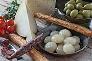 Assorted italian cheese (caciocavallo and Bastardo cheese), smoked sausages, cipolle borettane ( a variety of pickled onions), green olives, cherry tomatoes and bread sticks.