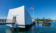 Aboard the USS Arizona Memorial, contemplate the rusting gun turret #3 of USS Arizona, sunk on 7 December 1941, yet still leaking oil, in Pearl Harbor, Oahu, Hawaii, USA. The USS Arizona Memorial marks the watery grave of 1102 sailors and Marines killed onboard that battleship during the Japanese surprise attack on Pearl Harbor, 7 December 1941. The attack united a divided America to join World War II. As a tribute to 1177 lost crew, the American flag flies from a flagpole attached to the severed mainmast of the sunken battleship. In one of history's greatest salvage jobs, all but 3 of the 21 ships sunk or damaged at Pearl Harbor were repaired back into service (only the USS Arizona was unsalvageable, whereas the Oklahoma and Utah were judged obsolete). More than two million people per year visit the 1962 USS Arizona Memorial, which is part of  the World War II Valor in the Pacific National Monument, run by the National Park Service. Reached only via boat, the memorial straddles but doesn't touch the sunken hull. USS Arizona (BB-39) was a Pennsylvania-class battleship launched by the United States Navy in 1916. A Japanese bomb violently exploded a powder magazine and sank the ship, killing 1177 officers and crewmen. The undersea wreck is a National Historic Landmark. This image was stitched from multiple overlapping images.