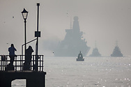 Royal Navy photographers capture HMS Dragon through the mist as she fires a gun salute on the return to her home port of Portsmouth for the first time in two months.  The Type 45 destroyer has been on a deployment involving exercises with the U.S. Navy and also a visit to the British Overseas Territory of Gibraltar.