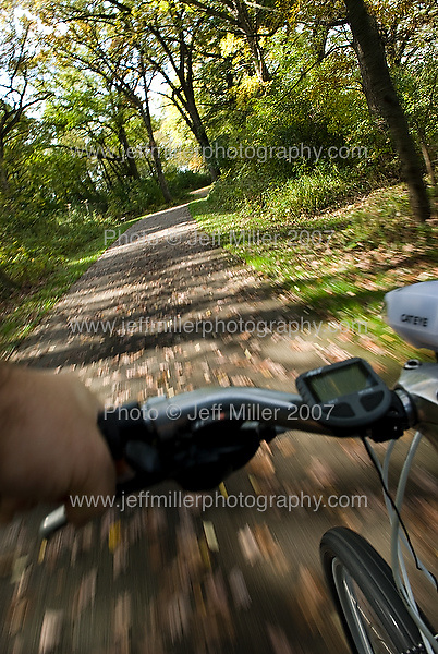 Fallen leaves and trees blur past as a bicycle passes along the Capital City bike trail through the southern edge of Madison, Wis., during autumn on Oct. 17, 2007..Photo © Jeff Miller 2007 - all rights reserved.www.jeffmillerphotography.com  ?  608-250-2374.Date: 10/07   File#: NIKON D200 digital camera frame 8771