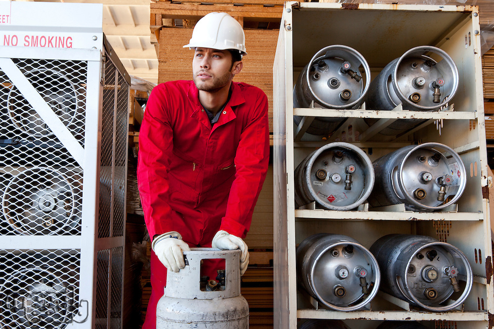 Hispanic worker inspecting gas canister
