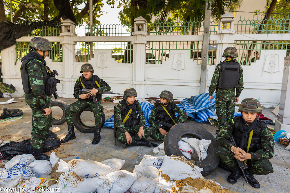 23 MAY 2014 - BANGKOK, THAILAND:  Thai soldiers relax near the Government House complex in Bangkok Friday. The Thai military seized power in a coup Thursday evening. They suspended the constitution and ended civilian rule. This is the 2nd coup in Thailand since 2006 and at least the 12th since 1932. The army has ordered both anti-government protestors in Bangkok and pro-government protestors in the suburbs to go home and arrested leaders of both groups.   PHOTO BY JACK KURTZ