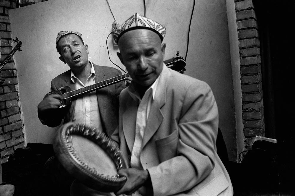 Xinjiiang Uygur Autonomous region. Kashgar. Musicians play a soulful piece at Uygur wedding.