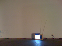 An old television with an antenna sits on the floor in front of a white wall.