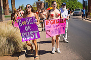 26 MARCH 2012 - PHOENIX, AZ:  MEGAN ERBE, left, and KELLY CAYE lead a march of topless women and men in Phoenix. About 40 people marched through central Phoenix Sunday to call for a constitutional amendment to give women the same right to go shirtless in public that men have. The Phoenix demonstration was a part of a national Topless Day of Protest. Phoenix prohibits women from going topless in public so protesters, women and men, covered their nipples and areolas with tape. The men did it to show solidarity with the women marchers.   PHOTO BY JACK KURTZ